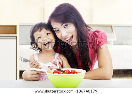 Smiling young asian mother and her daughter with fruit salad. shot in the kitchen - stock photo