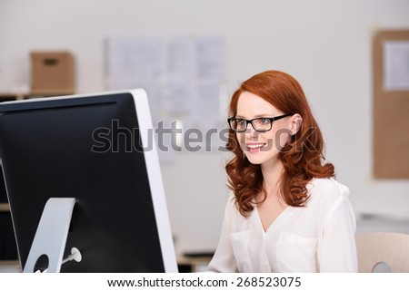 Smiling young attractive redhead businesswoman in glasses sitting working at her desktop computer in the office - stock photo