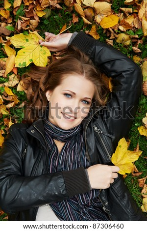 Smiling young attractive woman lying down on autumn maple leaves in park at fall outdoors