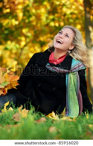 Smiling young attractive woman with autumn maple leaves in park at fall outdoors - stock photo