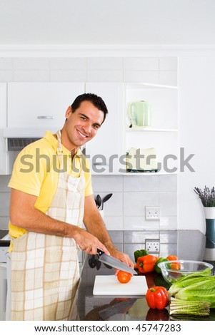 smiling young bachelor cooking in modern kitchen - stock photo
