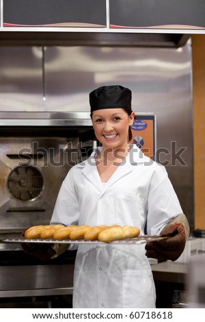 Smiling young baker with baguettes in the kitchen - stock photo
