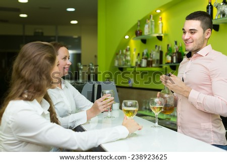 Smiling young bartender and two beautiful girls with wine at bar. Focus on man