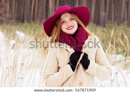 Smiling young, beautiful and stylish red hair girl in coat and hat in the forest. Fashion.