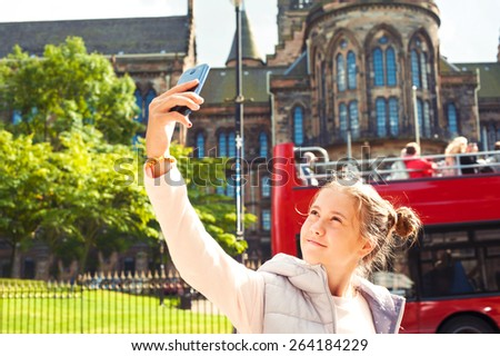 Smiling young beautiful girl taking self portrait in Glasgow historical place. Traveling. Summertime outdoors. - stock photo