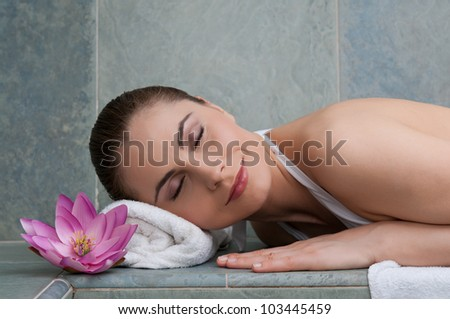 Smiling young beautiful lady relaxing at turkish bath at spa