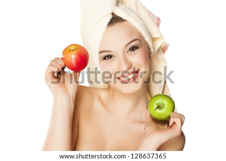 smiling young beautiful woman with a towel on her head, holds two apples in her hands