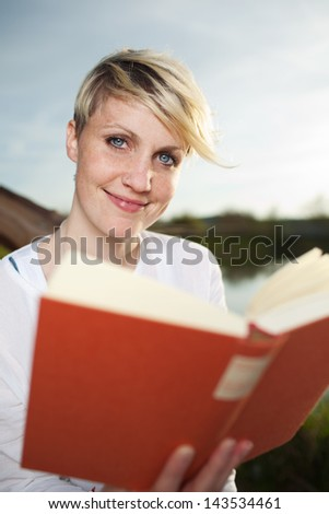 Smiling young beautiful young blond woman reading a book by the country lake - stock photo