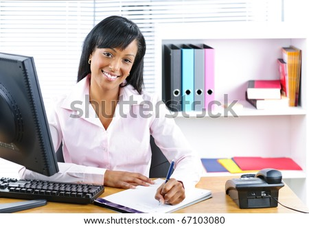 Smiling young black business woman writing at desk in office - stock photo
