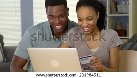 Smiling young black couple using credit card to make online purchases - stock photo