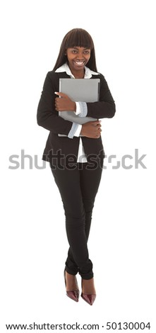 Smiling young black female student with closed laptop against chest - stock photo