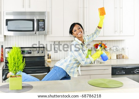 Smiling young black woman dancing and enjoying cleaning kitchen - stock photo