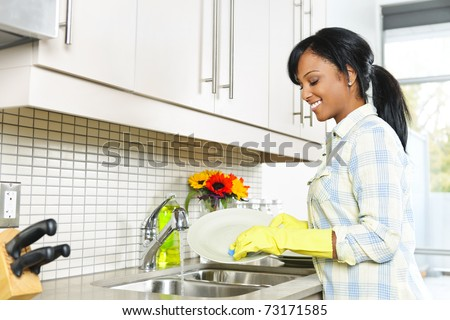 Smiling young black woman washing dishes in kitchen - stock photo