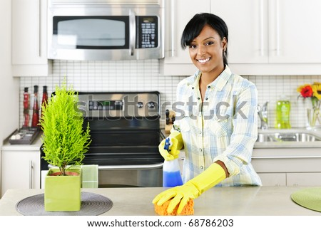 Smiling young black woman with sponge and rubber gloves cleaning kitchen - stock photo
