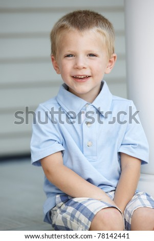 Smiling young blond boy sitting on porch steps at home on sunny day. - stock photo