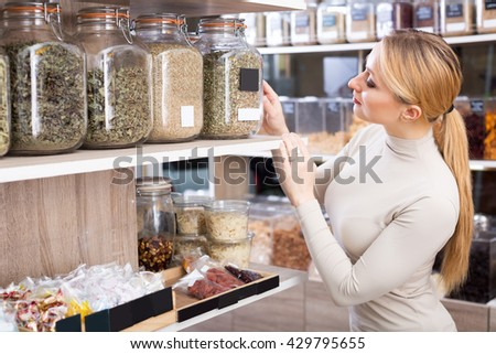 Smiling young blond woman choosing dried herbs sold by weight in organic shop - stock photo