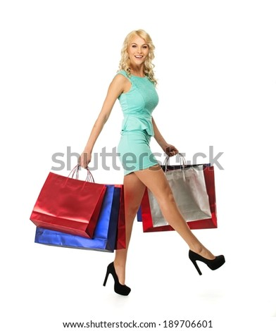 Smiling young blond woman on high heels with shopping bags