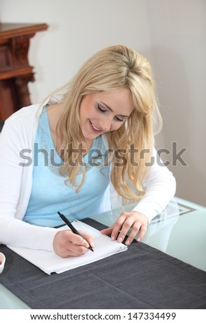 Smiling young blond woman sitting writing in a notepad seated at her dining room table at home