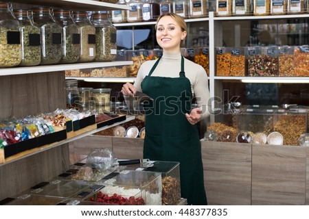 Smiling young blond woman wearing apron and selling nuts and dried fruits in organic shop