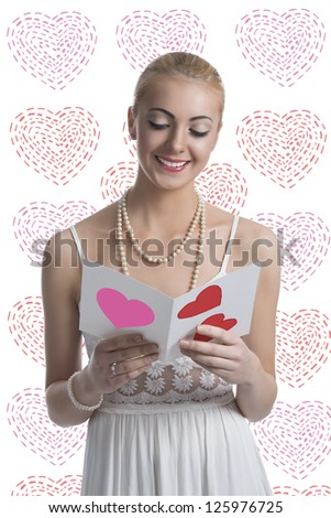 smiling young blonde girl with white dress reading valentine postcard. Some heart shaped decorations on background - stock photo