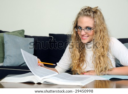 Smiling Young blonde student turning page in book