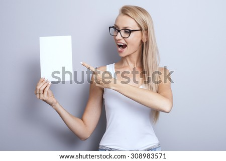 Smiling young blonde woman holding white empty board. Girl wearing fashionable eyeglasses. Studio shot. - stock photo