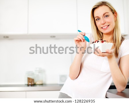 Smiling young blonde woman standing in her kitchen eating a healthy breakfast of cereal topped with yoghurt and fresh berries - stock photo