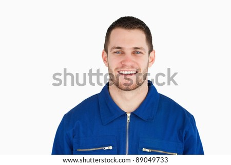 Smiling young blue collar worker against a white background - stock photo