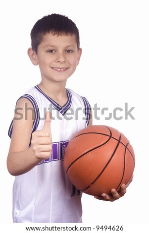 Smiling young boy holding his basketball - stock photo