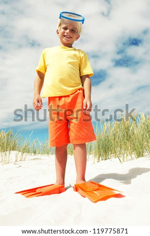 Smiling young boy in bright orange and yellow clothing posing on the beach in his flippers and snorkel - stock photo