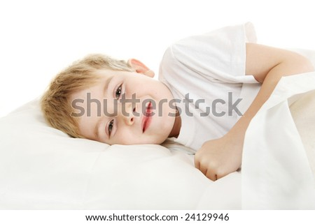 Smiling young boy laying in bed - stock photo