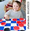 Smiling young boy playing checkers while sitting on rocking chair on porch - stock photo