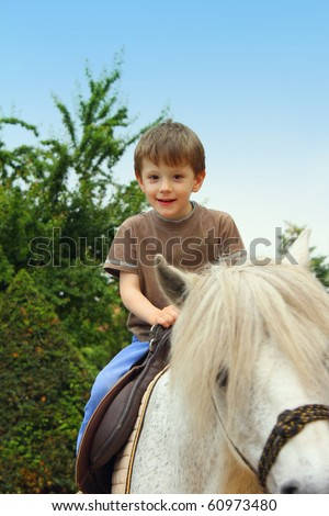 Smiling, young boy ride a pony horse - stock photo