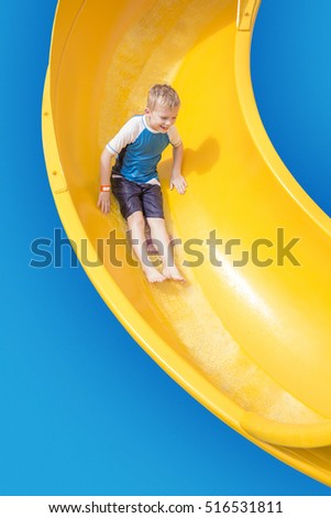 Smiling Young boy riding down a yellow water slide
