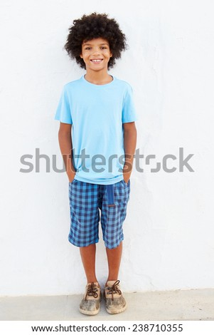 Smiling Young Boy Standing Outdoors Against White Wall - stock photo