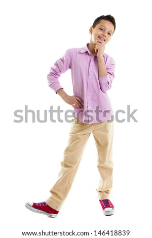 Smiling young boy with one hand holding the chin and the other on the hips, positive attitude, full lenght, isolated on white - stock photo