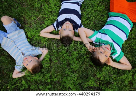 Smiling young boys lying on green grass and looking to the camera. Dreaming adorable brothers lying on grass, top view - stock photo