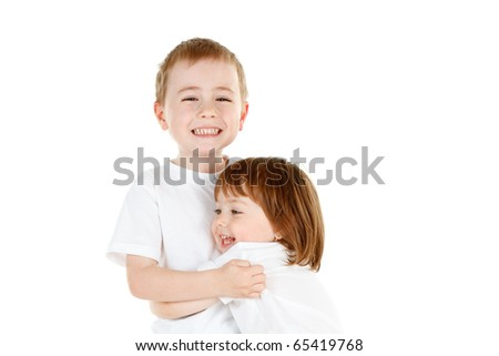 Smiling young brother and sister, both wearing white, in a hug.  Isolated on a white background.