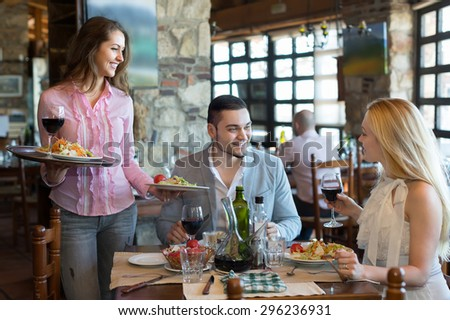 Smiling young brunette female waiter serving restaurant guests. Selective focus