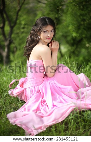 Smiling young brunette girl resting and sitting on green grass at spring park. Attractive model. - stock photo