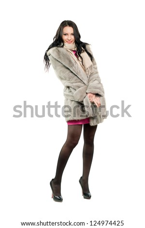 Smiling young brunette in a fur coat. Isolated - stock photo