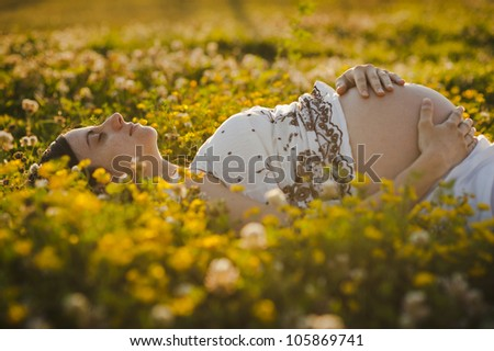 Smiling young brunette pregnant lying down over the flowers - stock photo