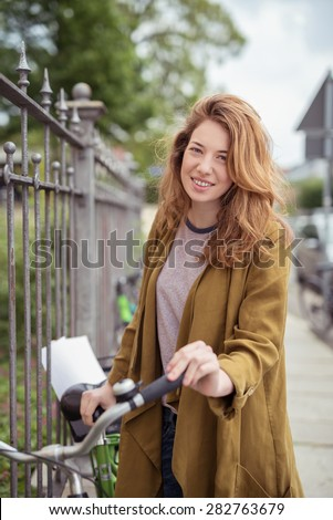 Smiling Young Brunette Woman Standing Next to Bicycle Leaning Against Iron Fence - stock photo