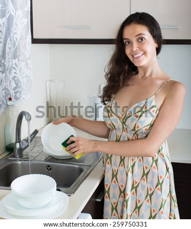 Smiling young brunette woman washing dishes in the kitchen - stock photo