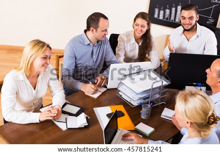 Smiling young business colleagues during conference call indoors - stock photo