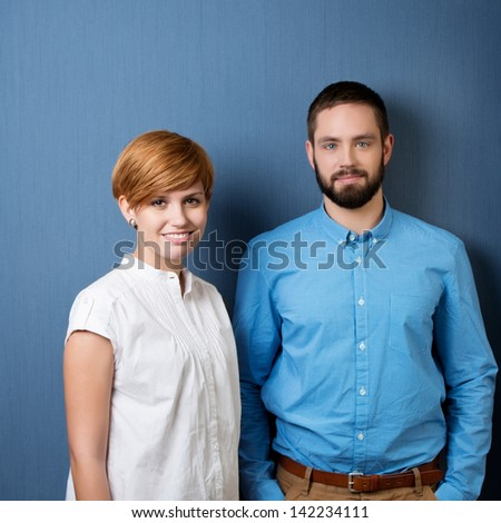 smiling young business man and woman with blue background - stock photo