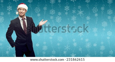 smiling young business man in santa hat showing empty space over winter snowflakes background - stock photo