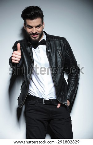 Smiling young business man leaning on a wall with his hand in pocket while showing the thumbs up gesture. - stock photo
