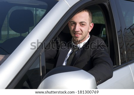 Smiling young business man looking from a car window