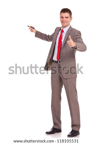 smiling young business man presenting something with marker pen and giving the thumbs up - stock photo